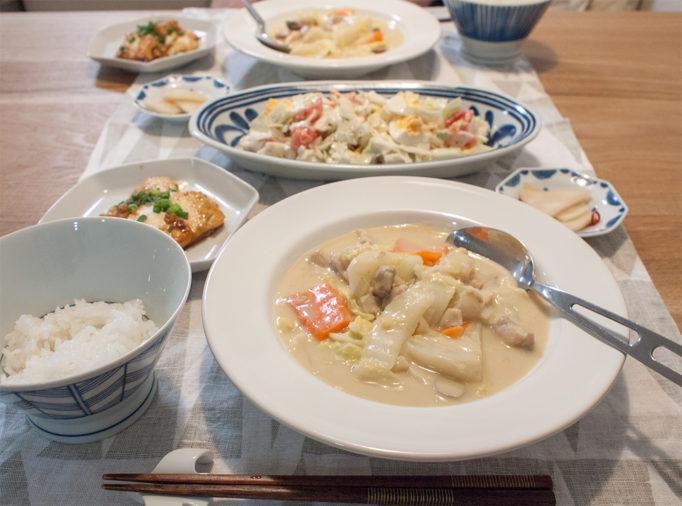 クリーム煮とサラダとお漬物と豆腐ステーキが並ぶ食卓