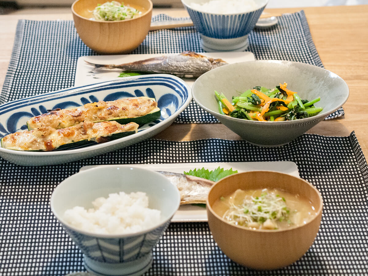 焼き魚とズッキーニのグラタンと小松菜のナムルが並ぶ食卓