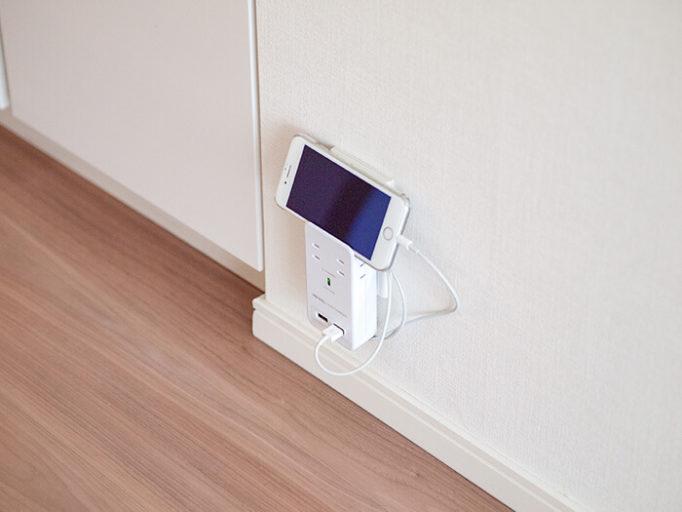 スマホを充電しながら立てかけられる電源タップを使っているところ