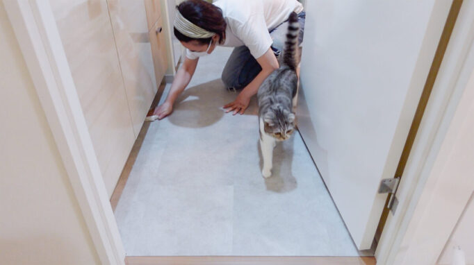 洗面所の床にフロアタイルを敷いたところ貼ってるところ